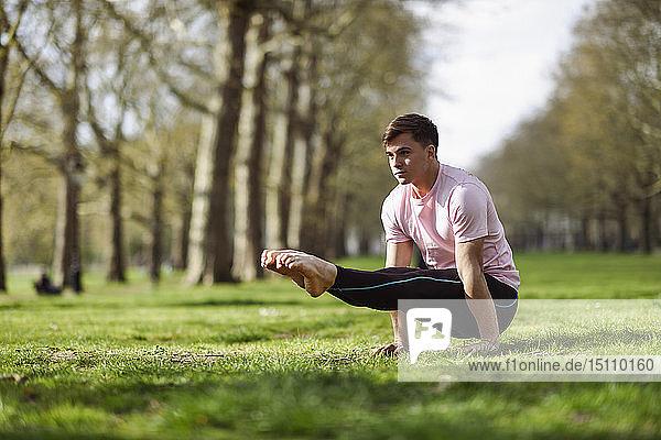 Junger Mann macht Gymnastikakrobatik in einem städtischen Park