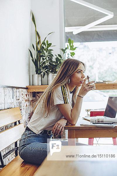 Junge Frau trinkt Kaffee im Café