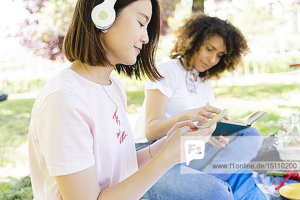 Two women with book and headphones relaxing in park