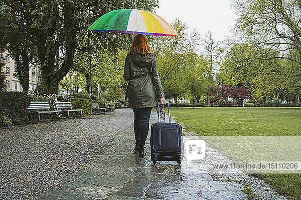 Junge Frau geht an einem regnerischen Tag im Stadtpark spazieren