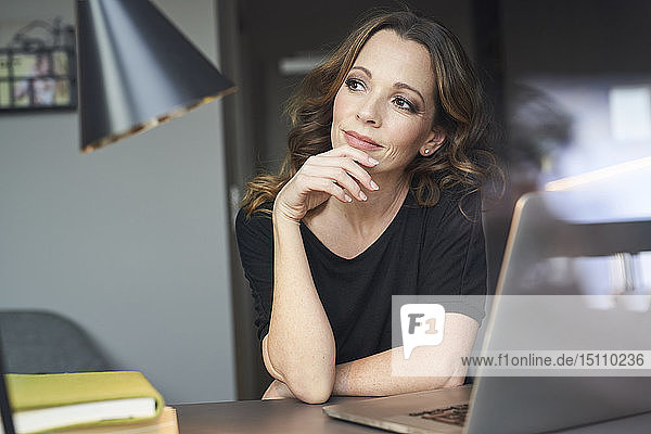 Woman with laptop at table at home thinking