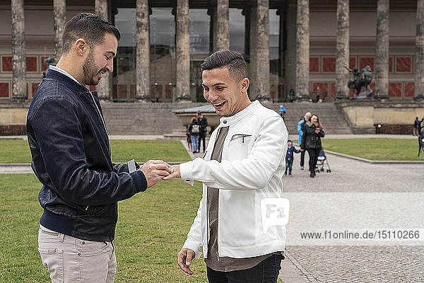 Young man putting on ring to his happy boyfriend at Lustgarten  Berlin  Germany
