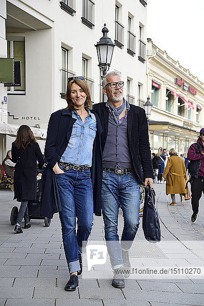Mature couple walking in the city  with arms around
