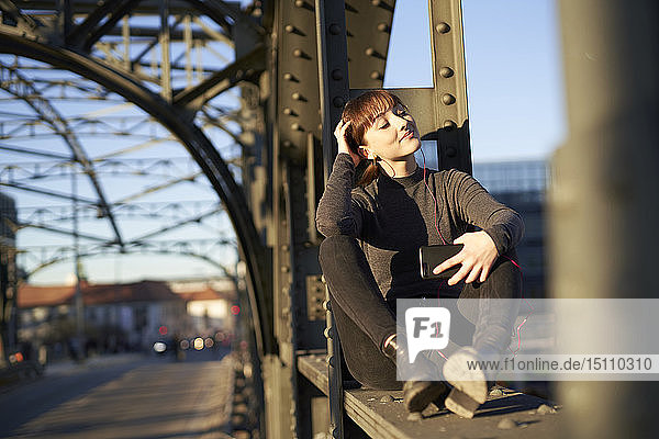 Portrait of relaxed young woman sitting on steel girder of a bridge listening music with smartphone