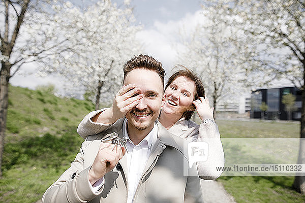 Happy young man holding latchkeys for new house  while woman is covering his eyes