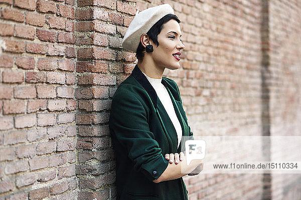 Fashionable young woman wearing a beret and a green jacket at a brick wall