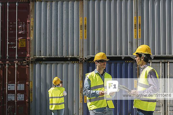 Arbeiter unterhalten sich in der Nähe eines Stapels von Frachtcontainern auf einem Industriegelände