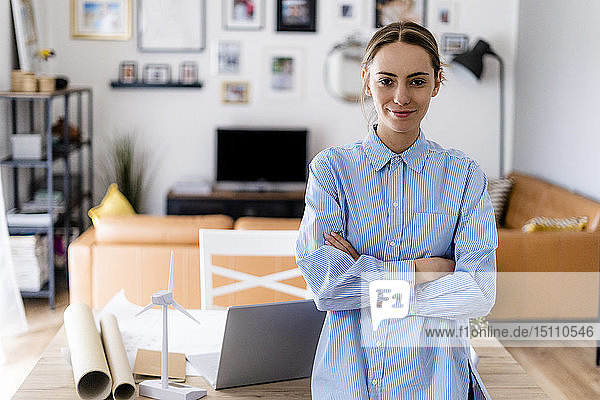 Portrait of confident woman standing in office with wind turbine model on table