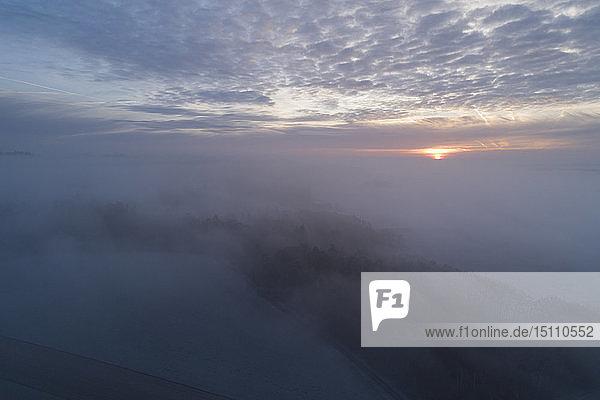 Deutschland  Bayern  Sonnenaufgang über nebliger Landschaft  Luftaufnahme