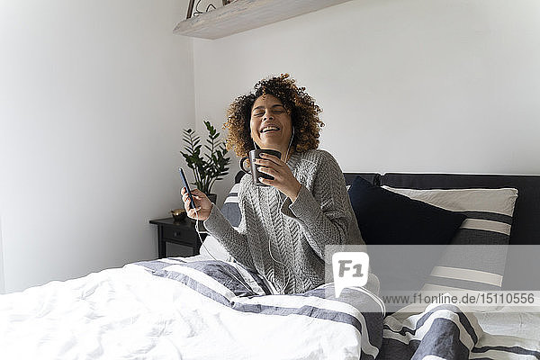Woman sitting on bed  drinking coffee  using smartphone and earphones