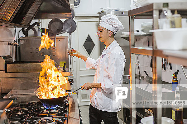 Junior chef with pan of flames in traditional spanish restaurant kitchen