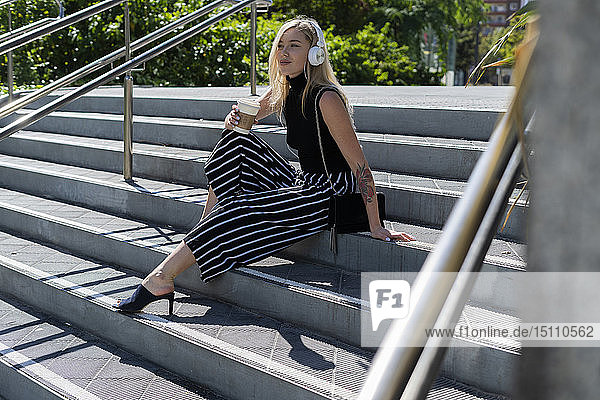 Blonde junge Frau mit Kaffee  die auf der Treppe sitzt und mit Kopfhörern Musik hört