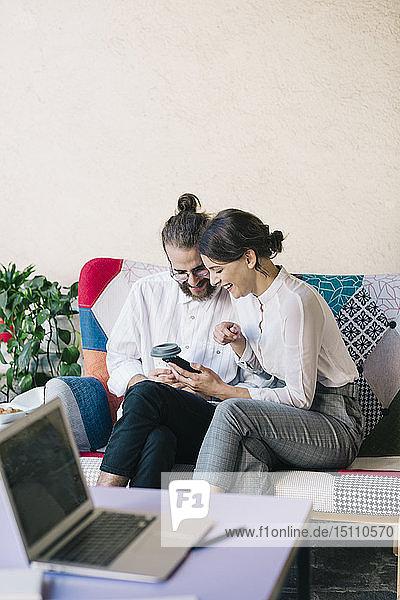 Junges Paar sitzt auf einem Sofa und benutzt ein Smartphone