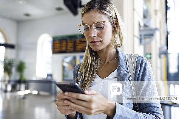 Junge Frau schreibt mit ihrem Mobiltelefon in der Bahnhofshalle