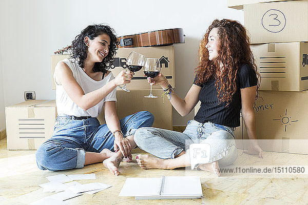Two friends moving into new home clinking red wine glasses