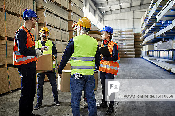 Workers talking in factory warehouse