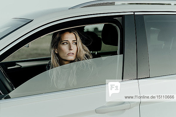 Blond woman in white car looking out of the window