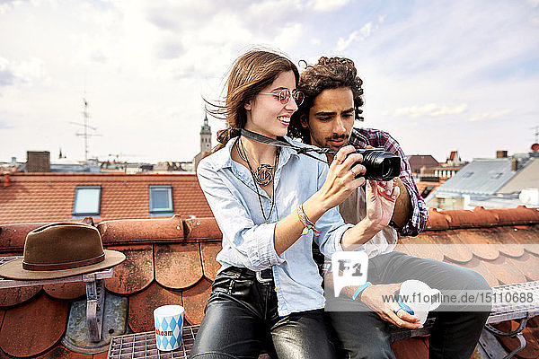 Young couple sitting on rooftop and taking pictures