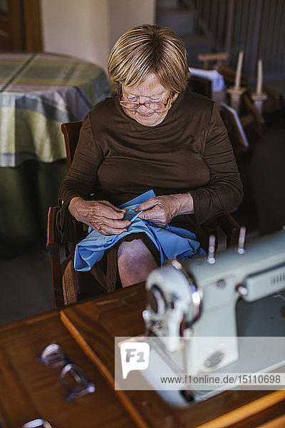 Senior woman working on garment at home