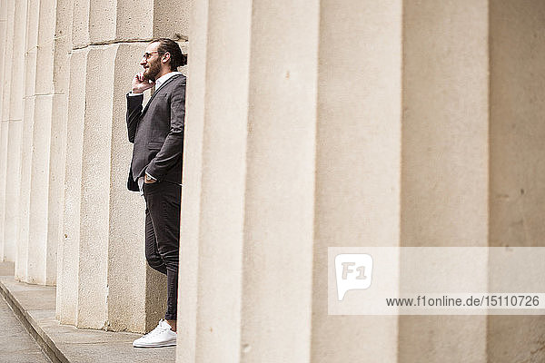 Junger Geschäftsmann am Telefon  der zwischen den Säulen der Börse steht  New York City  USA