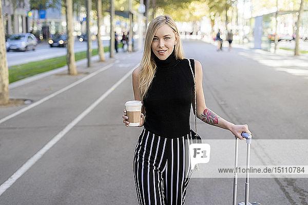 Porträt einer lächelnden blonden Frau mit Kaffee zum Mitnehmen und Rollgepäck