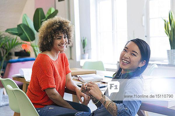 Zwei glückliche Frauen in einem modernen Büro mit Videoprojektor auf dem Tisch