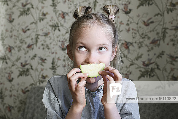 Portrait of blond girl with slice of courgette