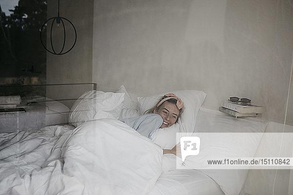 Glückliche junge Frau liegt im Bett