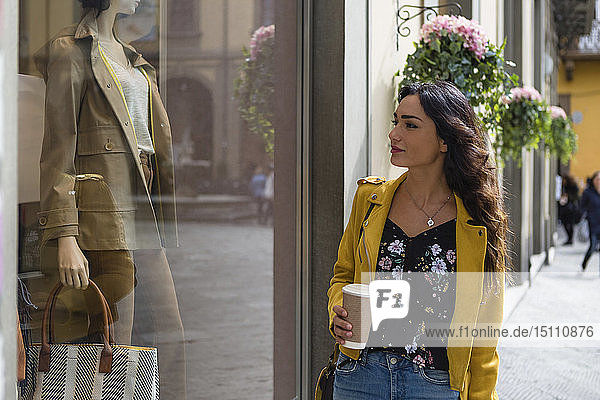 Portrait of young woman wearing yellow leather jacket  holding cup of coffee during shopping