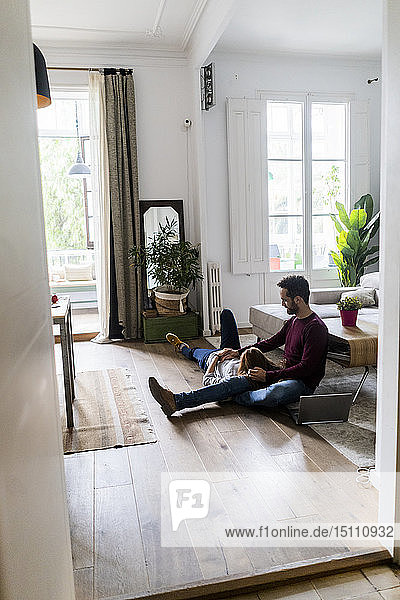 Zärtliches Paar mit Laptop  das sich zu Hause auf dem Boden entspannt