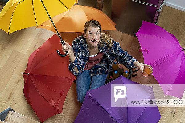 Junge Frau mit Regenschirmen auf dem Boden sitzend