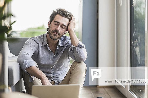 Young man sitting at home on floor  using laptop  taking a break