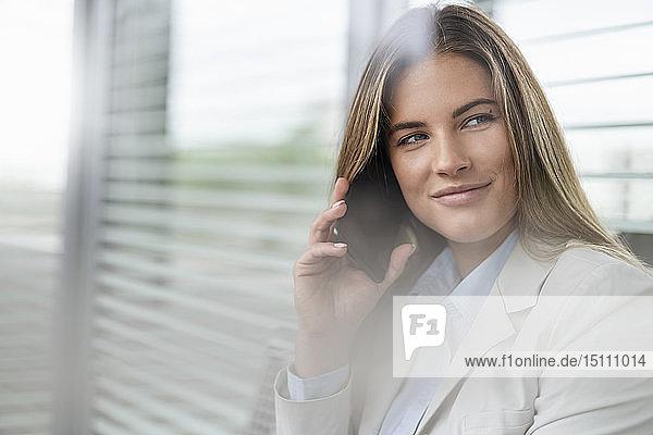 Junge Geschäftsfrau benutzt Smartphone in einem Wartebereich