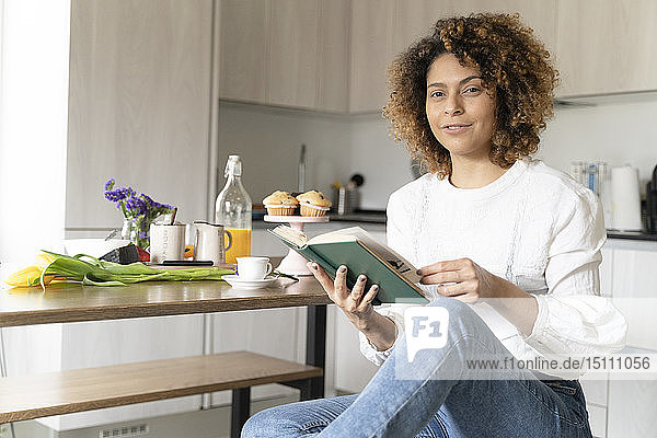 Woman sitting in kitchen  reading book
