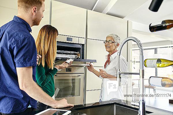 Verkäuferin  die den Ofen erklärt  um den Einkauf für eine neue Küche im Ausstellungsraum zu verbinden