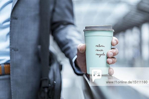 Nahaufnahme eines Geschäftsmannes mit einer wiederverwertbaren Kaffeetasse zum Mitnehmen Nahaufnahme eines Geschäftsmannes mit einer wiederverwertbaren Kaffeetasse zum Mitnehmen