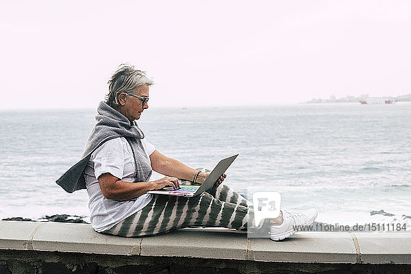 Ältere Frau sitzt auf einer Mauer am Meer und benutzt einen Laptop