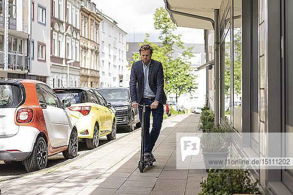 Geschäftsmann mit E-Scooter auf Bürgersteig