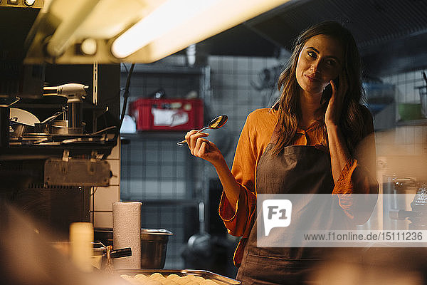 Junge Frau telefoniert in Restaurantküche mit ihrem Handy