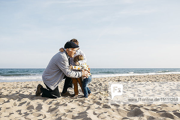 Grandfather hugging his grandchildren on the beach in spring