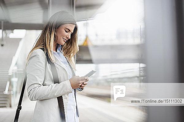 Junge Geschäftsfrau mit Tablette am Bahnhof stehend