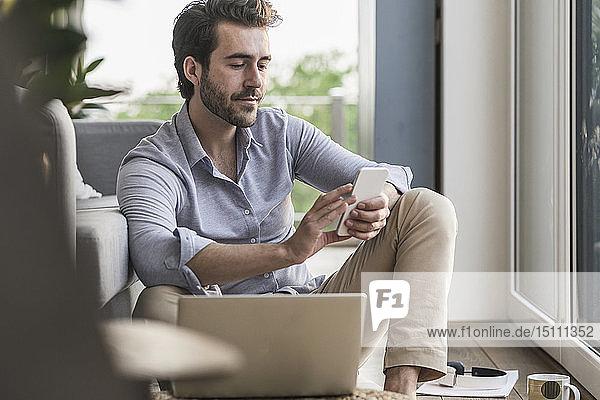 Junger Mann sitzt zu Hause auf dem Boden und benutzt ein Smartphone