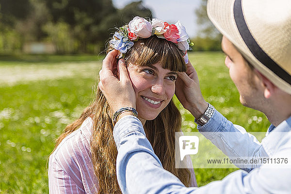 Junger Mann legt seiner Freundin Blumen auf den Kopf