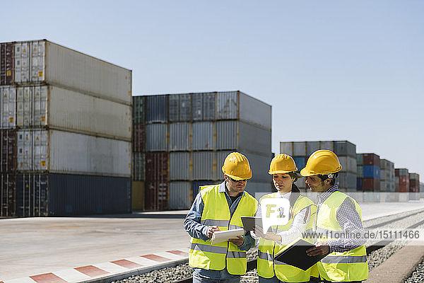 Arbeiter an Bahngleisen in der Nähe von Frachtcontainern auf einem Industriegelände