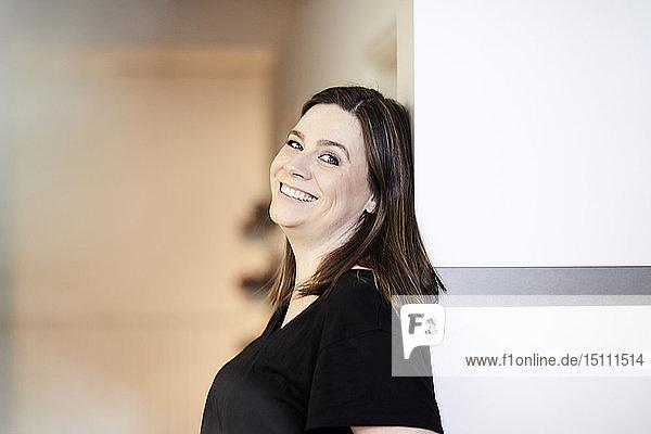 Porträt einer lächelnden Frau in einem an die Wand gelehnten Büro