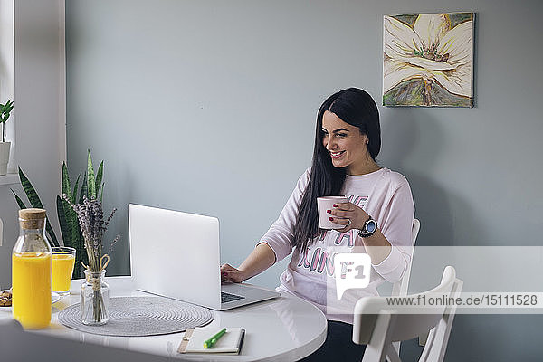 Beautiful young woman browsing in internet and drinking coffee at home