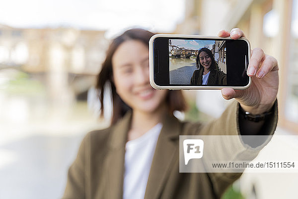 Italy  Florence  young tourist woman taking a selfie at Ponte Vecchio