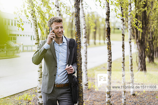 Businessman on cell phone in a park