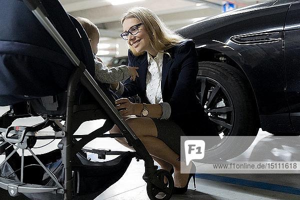 Glückliche junge Geschäftsfrau mit Kleinkind im Kinderwagen auf einem Parkplatz