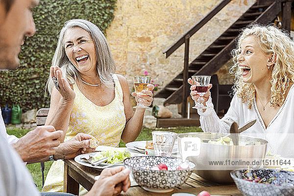 Fröhliche Familie beim gemeinsamen Essen im Garten Fröhliche Familie beim gemeinsamen Essen im Garten